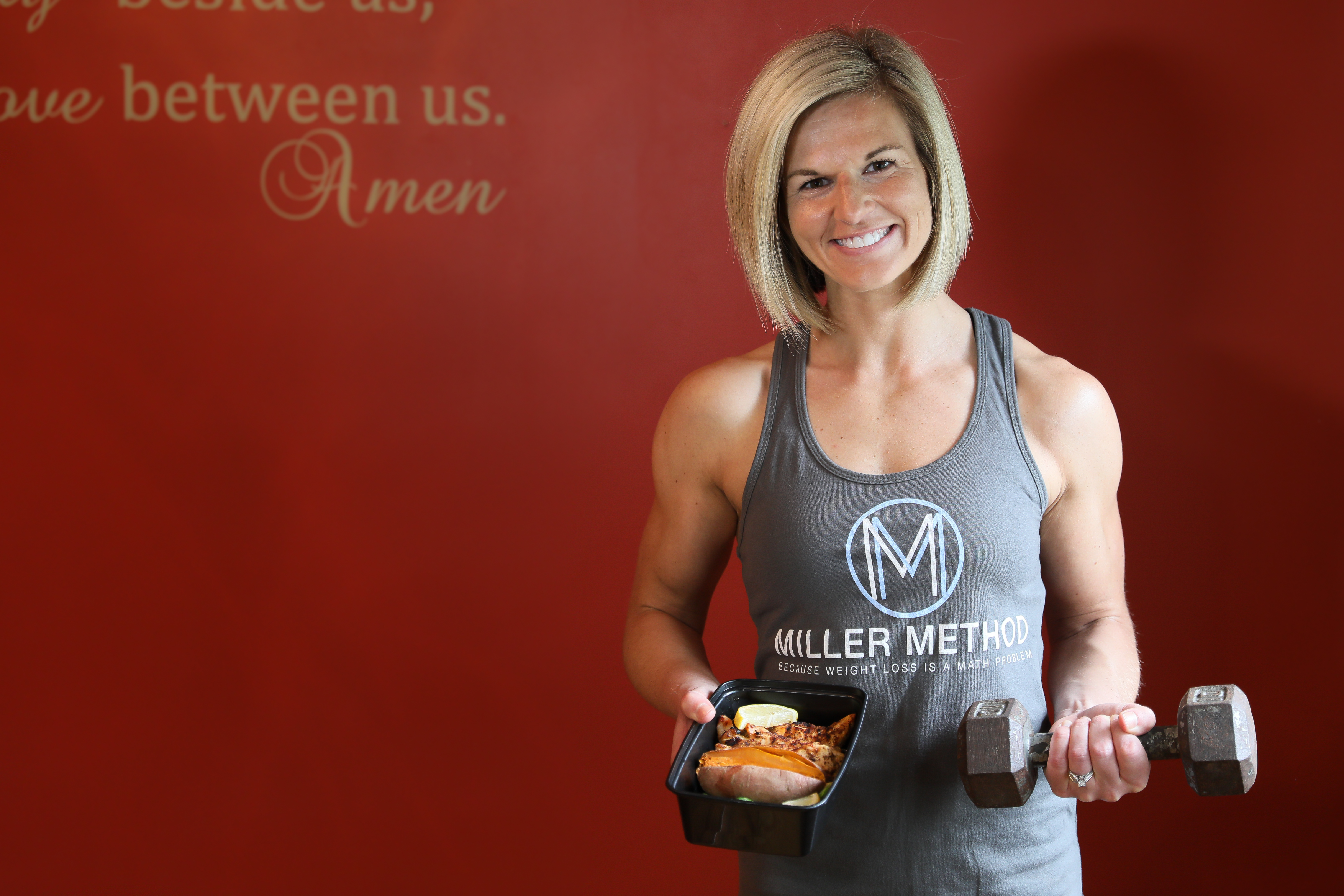 "Julie poses in front of a red wall holding a container of food in one hand and a small dumbbell in the other. She is smiling and wearing a gray tank top that reads ""Miller Method"""